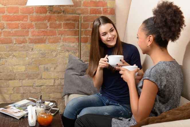 Friends in coffee shop. Two young female friends sitting in cafe and talking to each other and laughing