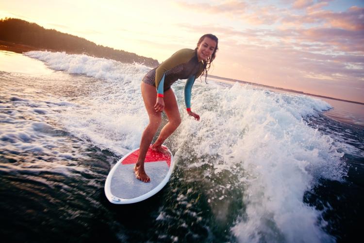 Pretty female enjoying surfing on summer vacation