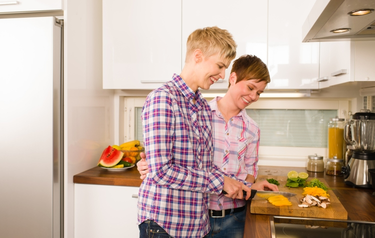 Happy lesbian couple makes a dinner in the kitchen horizon format ** Note: Shallow depth of field